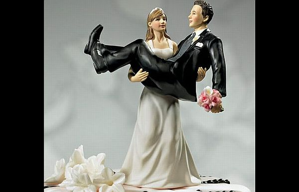 Bride holding groom in hands wedding cake topper