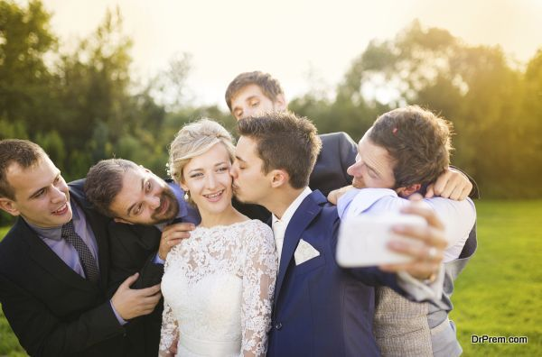 Bride with groom and his friends taking selfie