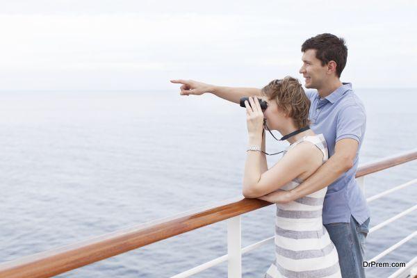 couple enjoying cruise, woman looking through binoculars and man showing something ahead