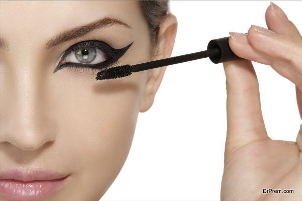 Beautiful model applying mascara on eyelashes close up