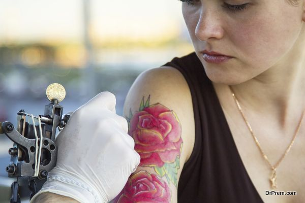 tattooer showing process of making a tattoo on young beautiful hipster woman with red curly hair arm. Tattoo design in the form of rose