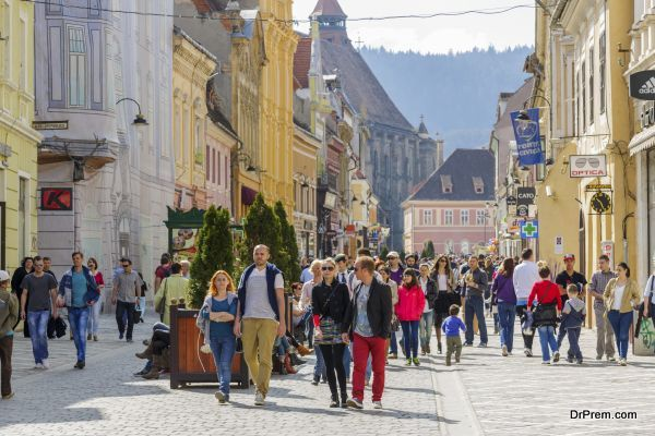 BRASOV, ROMANIA - MARCH 23: Unidentified tourists stroll and enjoy the sights along Republic Street on March 23, 2014 in Brasov, the 7th largest and the most visited city in Romania.